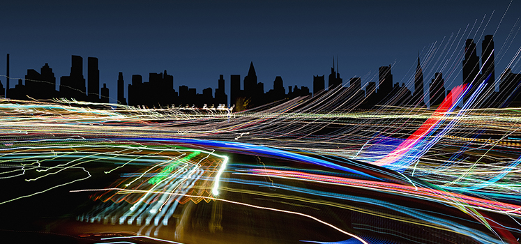 Light trails under New York City skyline at night, New York, United States